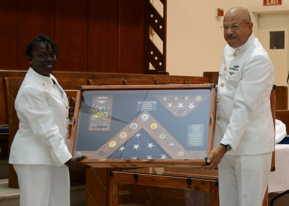 Senior Chief Hospital Corpsman Charles Wyllie (right) presents a retirement shadow box to Naval Hospital Jacksonville, Fla., Command Master Chief Bennora Simmons during her retirement ceremony, July 31. Simmons, a native of Charleston, S.C., retired after 30 years of naval service.