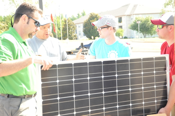 Daniel Tate, center, of the Alabama Center for Sustainable Energy, Raul Alonso, left and Dominic Ragucci, right, U.S. Army Engineering and Support Center, Huntsville help volunteer assemble solar panel August 8.