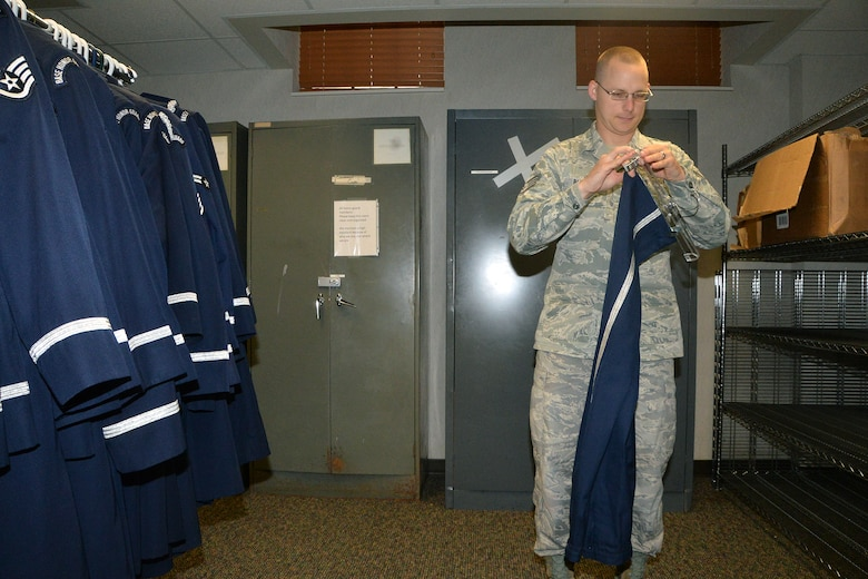 U.S. Air Force Staff Sgt. Christopher Burke's, 55th Wing Honor Guard NCO in charge, hangs a pair of Honor Guard uniform pants Aug. 7 at Offutt Air Force Base, Nebraska. Burke collects uniforms from outgoing honor guard Airmen in order to pass them down to incoming guardsmen. (U.S. Air Force photo by Dana P. Heard)
