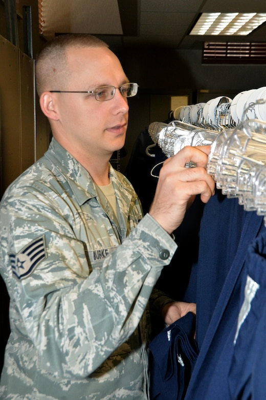 U.S. Air Force Staff Sgt. Christopher Burke's, 55th Wing Honor Guard NCO in charge, organizes a clothing rack full of Honor Guard uniforms Aug. 7 at Offutt Air Force Base, Nebraska. Burke invested approximately $500 in organizing the uniform supply closet and has saved the Air Force more than $15,000. (U.S. Air Force photo by Dana P. Heard)