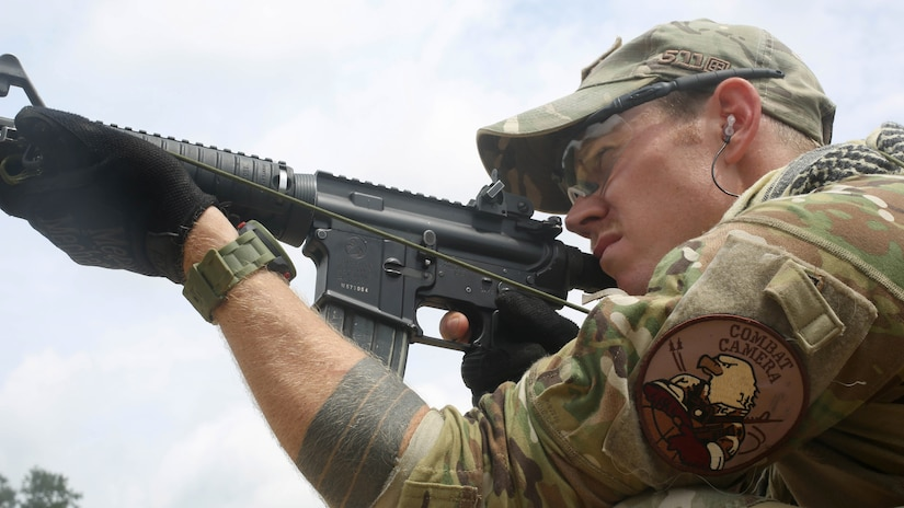Air Force Staff Sgt. Sam Weaver, a Combat Camera Airman, assigned to the 1st Combat Camera Squadron, shoots his M4 carbine rifle during the 3rd Annual Spc. Hilda I. Clayton Best Combat Camera (COMCAM) Competition qualification range at Fort George G. Meade, Md., July 14, 2015. Weapons qualification is conducted on day two of the Spc. Hilda I. Clayton Best COMCAM Competition, where teams of two compete throughout a weeklong event that assesses the technical and tactical skills of visual information personnel. The Competition is established in honoring fallen combat camera Soldier Spc. Hilda I. Clayton, who gave her life July 2, 2013, in Afghanistan as a part of Operation Enduring Freedom. (U.S. Army photo / Staff Sgt. Kwadwo Frimpong) 