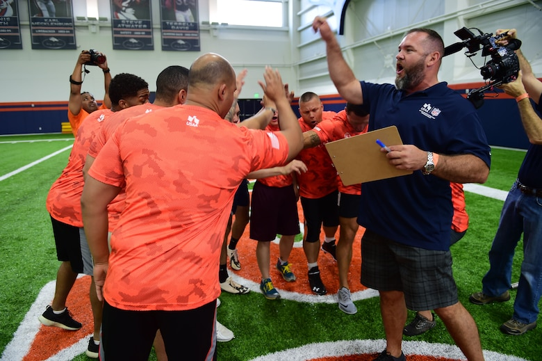 A former Denver Broncos player, assisting with the military combine, gets military members excited before the bench press portion of the combine Aug. 7, 2015, at the Broncos Headquarters Facility at Dove Valley in Denver. The combine consisted of drills similar to the ones prospective National Football League players are expected to complete during the NFL combine held in Indianapolis before the NFL draft. All participants were also treated to a viewing of the Broncos' Friday morning practice and a visit from Broncos players, as well as the head coach. (U.S. Air Force photo by Airman 1st Class Luke W. Nowakowski/Released)