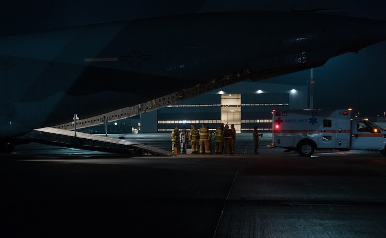 Firefighters from the 86th Civil Engineer Squadron Kaiserslautern Military Community Fire Emergency Services stand by after transporting a wounded warrior from a C-17 Globemaster III to an ambulance on August 9, 2015 on Ramstein Air Base, Germany. Ramstein fire and medical personnel from the 10th Aeromedical Evacuation Operations Team and the 455th Critical Care Air Transport Team assisted with the aeromedical evacuation out of Afghanistan. (U.S. Air Force photo/Staff Sgt. Leslie Keopka)