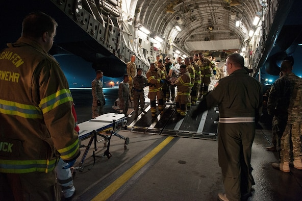 Firefighters and medical personnel transport a wounded warrior from a C-17 Globemaster III to an ambulance on August 9, 2015 on Ramstein Air Base, Germany. Personnel from the 86th Civil Engineer Squadron Kaiserslautern Military Community Fire Emergency Services and personnel from the 10th Aeromedical Evacuation Operations Team and the 455th Critical Care Air Transport Team Ramstein assisted with the aeromedical evacuation out of Afghanistan. (U.S. Air Force photo/Staff Sgt. Leslie Keopka)