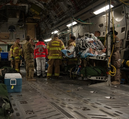 Firefighters and medical personnel standby to assist in the transport of a patient during an aeromedical evacuation mission on August 9, 2015 at Ramstein Air Base, Germany. The personnel assisting in the mission were from the 86th Civil Engineer Squadron, Kaiserslautern Military Community Fire Emergency Services and personnel from the 10th Aeromedical Evacuation Operations Team and 455th Critical Care Air Transport Team. (U.S. Air Force photo/Staff Sgt. Leslie Keopka)