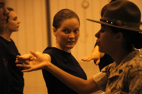 Sgt. Rosario Battiest, a Company N, 4th Recruit Training Battalion, Marine Corps Recruit Depot Parris Island drill instructor,corrects a poolees drill deficiency during Marine Corps Recruiting Station Kansas City's all-hands female pool function at Camp Clark in Nevada, Mo., Aug. 7, 2015.