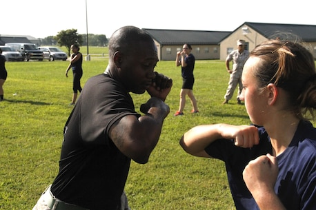 Staff Sergeant Norris L. Russell Jr., a Marine Corps Recruiting Station Kansas City recruiter, demonstrates a proper horizontal elbow strike to a poolee during RS Kansas City's all-hands female pool function at Camp Clark in Nevada, Mo., Aug. 7, 2015.