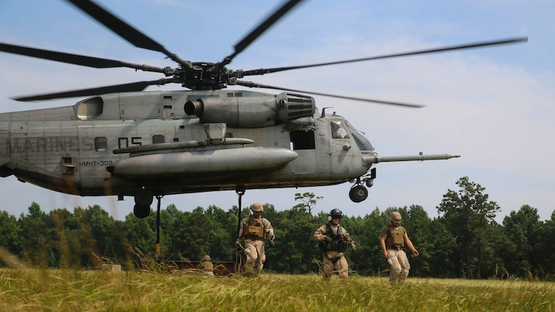 Marines onboard a CH-53E Super Stallion with Marine Heavy Helicopter Training Squadron 302 participate in an external lift exercise with Combat Logistics Battalion 6 at Marine Corps Base Camp Lejeune, North Carolina, Aug. 5, 2015. Two student pilots onboard the helicopter performed externals for the first time, an operation essential to deployed operations, and part of their pilot certification.