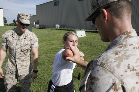 Gunnery Sergeant Nicholas McCulloch, a Marine Corps Recruiting Station Kansas City recruiter, instructs a poolee to strike his hand with a horizontal elbow strike as Staff Sgt. Adam Halter, a RS Kansas City recruiter, looks on and critiques during RS Kansas City's all-hands female pool function at Camp Clark in Nevada, Mo., Aug. 7, 2015.