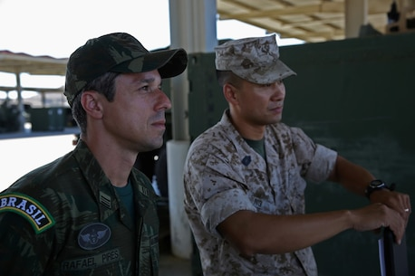 Master Sgt. Alex Ng, the field artillery chief assigned to Battery Q, 5th Battalion, 11th Marine Regiment, 1st Marine Division, explains the abilities of the M142 High-Mobility Artillery Rocket System to Maj. Rafael Pires Ferreira, a battery commander with Brazil's Corpo de Fuzileios, aboard Marine Corps Base Camp Pendleton, Calif., Aug. 5, 2015. Two Brazilian military officers participated in a Subject Matter Expert Exchange with the Marines and Sailors of 11th Marines to compare standard operating procedures and to share experiences and ideas.