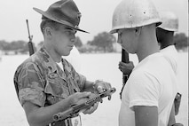 A drill instructor inspects a recruit's rifle in this early-1980's era photo.