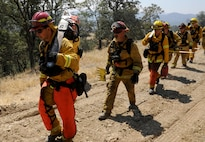 Steven Dobbs, a 9th Civil Engineer Squadron fire captain, carries a chainsaw up a hill in front of other fire prevention organization members Aug. 6, 2015, near Clearlake, Calif. The firefighters were sent to clear brush away from burned sections of land to prevent embers from igniting unburned areas. (U.S. Air Force photo/Airman Preston L. Cherry)