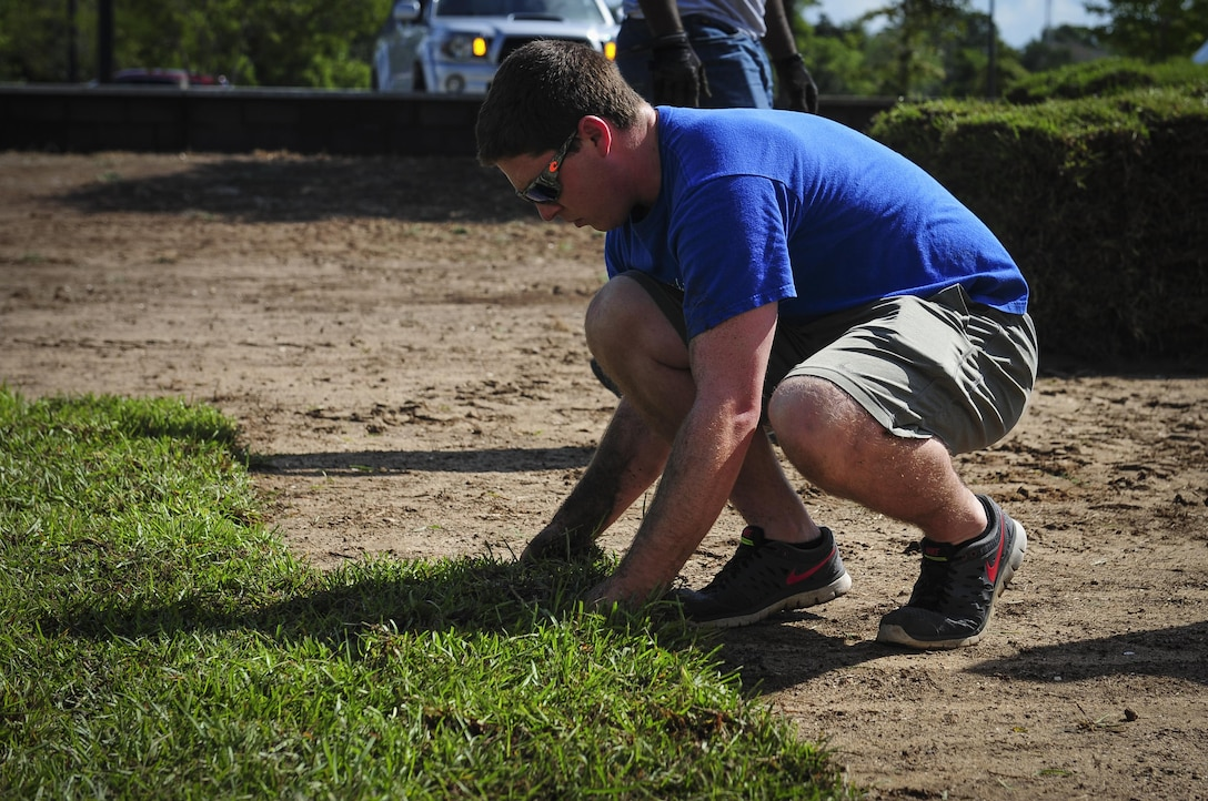 Senior Airman Brice Evans, 1st Special Operations Maintenance Group aircraft scheduler, places sod at Soundside Lodging on Hurlburt Field, Fla., Aug. 6, 2015. Approximately 30 Airmen from Hurlburt laid 19,800 square feet of sod at Soundside Lodging as part of Pride Epidemic. (U.S. Air Force photo by Senior Airman Meagan Schutter)