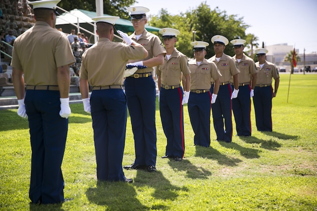 """Marines with 1st Tank Battalion perform the passing of the colors presentation during the reciting of """"Old Glory"""" during a retirement ceremony for 1st Sgt. Nelson A. Hidalgo, Company A First Sergeant, 1st Tanks, at Lance Cpl. Torrey L. Gray Field, Aug. 7, 2015. During the presentation, the flag was passed between Marines of every rank Hidalgo has held throughout his career. (Official Marine Corps photo by Pfc. Levi Schultz/Released)"""