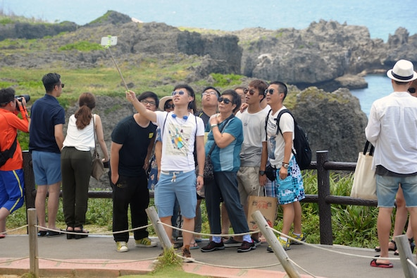 "A group of tourists poses for a ""selfie"" photo in front of the unique coral rock formations on Cape Manzamo Aug. 11, 2015. The cape is one of Okinawa's most popular tourist destinations. (U.S. Air Force photo by Tim Flack)"