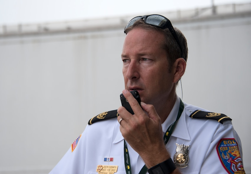 Joseph Suddarth, a 96th Civil Engineer Squadron assistant fire chief, communicates and coordinates with exercise planners and first responders during a simulated aircraft hijacking scenario as part of the 96th Test Wing's force protection condition exercise Aug. 6 at Eglin Air Force Base, Fla.  The FPCON exercise tested the base's first responders' rescue skills while the simulated hijacker was apprehended and the injured were moved to safety for treatment. (U.S. Air Force photo/Ilka Cole)