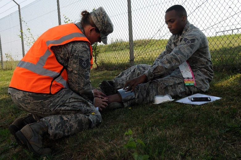 U.S. Air Force Tech. Sgt. Melissa Blackledge, an aerospace medical technician from the New Jersey Air National Guard's 177th Medical Group, assists a mock patient with a broken ankle during a simulated fuel spill on Spangdahlem Air Base, Germany, Aug. 7, 2015. Blackledge was embedded as part of the wing-inspection team for the scenario-based inspection. (U.S. Air National Guard photo by Senior Airman Shane S. Karp/Released)