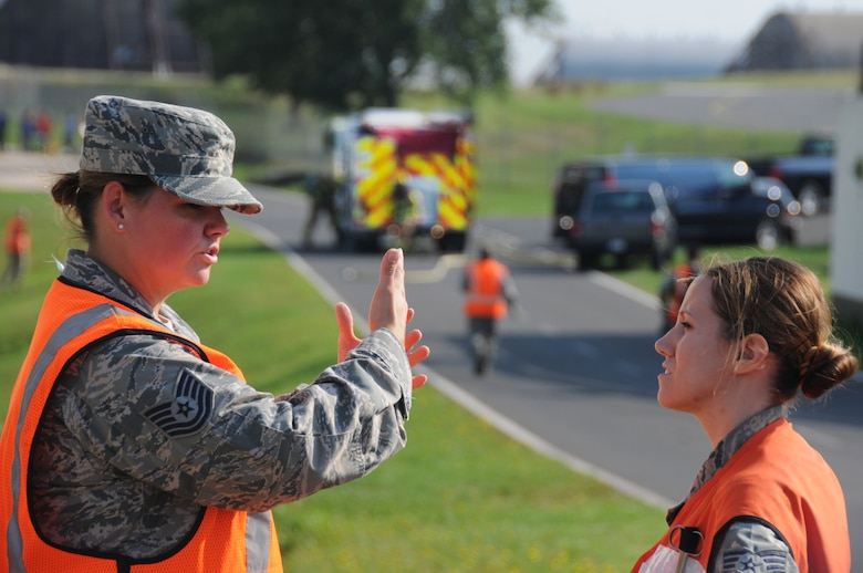 U.S. Air Force Tech. Sgt. Melissa Blackledge, left, and Senior Airman Melissa Seel, aerospace medical technicians from the New Jersey Air National Guard's 177th Medical Group, discuss operation strategy during a simulated fuel spill on Spangdahlem Air Base, Germany, Aug. 7, 2015. Members from the 177th integrated with the active-duty force for the scenario-based inspection. (U.S. Air National Guard photo by Senior Airman Shane S. Karp/Released)