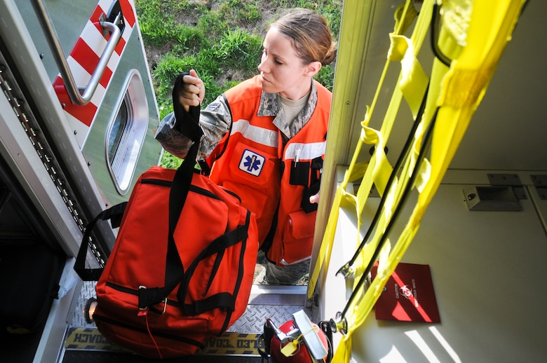 U.S. Air Force Senior Airman Melissa Seel, an aerospace medical technician from the New Jersey Air National Guard's 177th Medical Group, grabs her emergency medical bag before heading to the scene of a simulated fuel spill on Spangdahlem Air Base, Germany, Aug. 7, 2015. Members from the 177th integrated with the active-duty force for the scenario-based inspection. (U.S. Air National Guard photo by Senior Airman Shane S. Karp/Released)