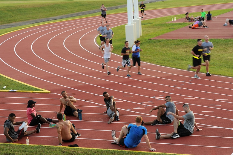 Several small groups of participants in the first session of Kadena Air Base's running improvement program work out and perform post-run stretches on the Kadena High School track, Aug. 5, 2015. The running improvement program is an eight-week program designed to improve particpants' run times while educating them on proper form. Historically, participants average a 1 minute 45 second improvement on their one and a half mile timed run. (U.S. Air Force photo by Airman 1st Class Zade C. Vadnais)