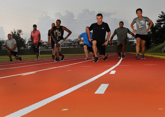 Participants in the first session of Kadena Air Base's running improvement program perform lunges as a warm up exercise before beginning their cardiovascular workout at the Kadena High School track, Aug. 5, 2015. The running improvement program is an eight-week program designed by a certified natural running coach that aims to improve participants' run times while educating them on proper form. (U.S. Air Force photo by Airman 1st Class Zade C. Vadnais)