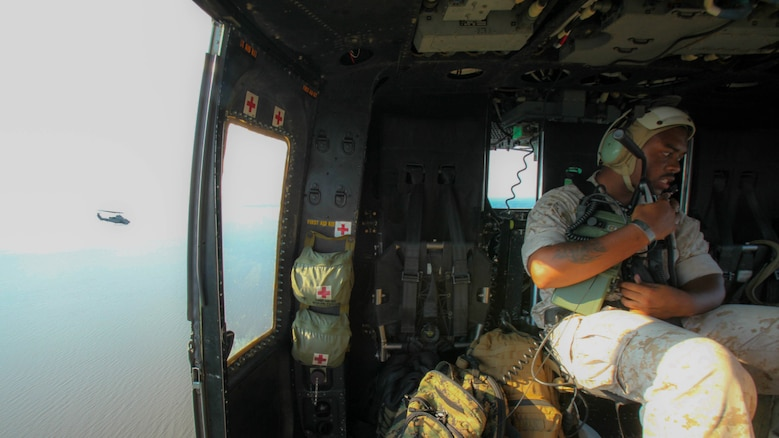 Sgt. Cyrus Brown operates an AN/PRC-117 G wideband tactical radio, inside a UH-1Y Huey while flying alongside an AH-1W Super Cobra during a training exercise testing a digital interoperability system at Marine Corps Air Station Cherry Point, N.C., July 24, 2015. Digital interoperability is the technology capable of increasing prowess on the battlefield.  The exercise included Marine Light Attack Helicopter Squadron 467, Marine Unmanned Aerial Vehicle Squadron 2, and U.S. Marine Corps Forces, Special Operations Command, testing a LINK 16 conversion system for one of the first times within an explicitly rotary-wing exercise.  Brown is a radio operator with VMU-2.