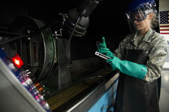 Airman 1st Class Danielle Harrington, a 2nd Maintenance Squadron nondestructive inspection apprentice, inspects a part prior to using a magnetic particle machine at Barksdale Air Force Base, La., July 21, 2015. NDI interprets and evaluates aircraft and equipment defects the visual eye can't see without dismantling the whole component. (U.S. Air Force photo/Senior Airman Jannelle Dickey)