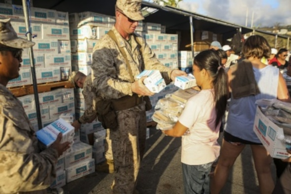 Marines hand out water to the residents of Saipan