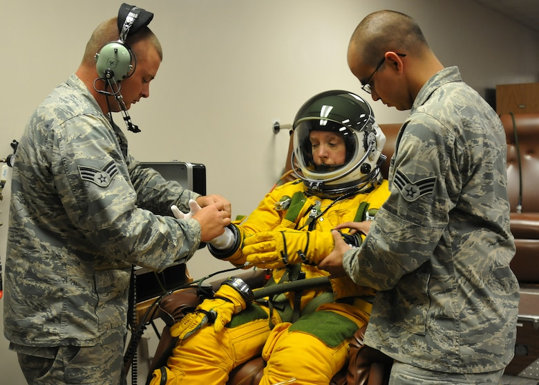 Senior Airmen Kyle Lang (right) and Aaron Saenz (left), 9th Physiological Support Squadron launch and recovery technicians, help Secretary of the Air Force Deborah Lee James properly dress in a high-altitude pressure suit at Beale Air Force Base, California, Aug. 11, 2015.  The specialized pressure suit allows U-2 Dragon Lady pilots to safely fly at altitudes reaching 70,000 feet. James visited Beale to receive a first-hand perspective of high-altitude intelligence, surveillance and reconnaissance from collection to dissemination. (U.S. Air Force photo by Senior Airman Dana J. Cable)