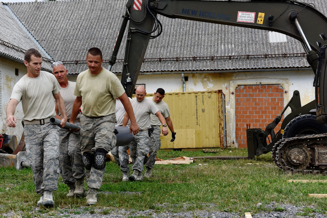 Members of the 140th Civil Engineer Squadron, Colorado Air National Guard (COANG) carry a roll of industrial floor vinyl into a barn at Pocek Range, near Postonja, Slovenia, July 23, 2015. The COANG is on a deployed for training mission as part of the Colorado State Partnership Program (SPP), revamping a historically old barn into a range center facility to conduct multinational training for on ground and air-to-ground tactics in the European theater. The SPP is focused on building relationships while supporting one another and improving the strategic objectives of both countries. (U.S. Air National Guard photo by Senior Airman Michelle Y. Alvarez-Rea/Released)
