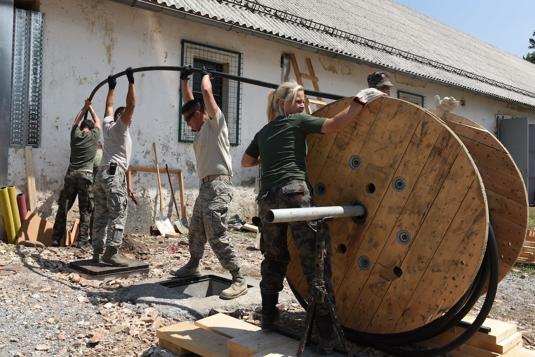 Members of the Colorado Air National Guard and  Slovenian Armed Forces (SAF) work together to pull a main power cable at Pocek Range, near Postonja, Slovenia, July 22, 2015. The SAF provided troops to assist Colorado Guardsmen restoring a historically old barn into a usable range facility to be used by SAF and NATO countries for joint, multinational training and exercises. (U.S. Air National Guard photo by Senior Airman Michelle Y. Alvarez-Rea/Released.)