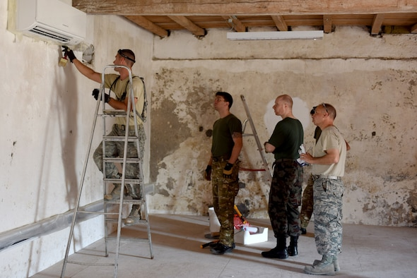U.S. Air Force Staff Sgt. William Bryant, 140th Civil Engineer Squadron, Colorado Air National Guard (COANG), demonstrates  paint and wall refinishing techniques to Slovenian Armed Forces (SAF) at Pocek Range, near Postonja, Slovenia, July 21, 2015. The deployed for training mission is focused on creating lasting relations between the U.S. and partner nations and restoring a historically old barn that has been used for multiple purposes over hundreds of years into a  usable range center facility that will be used by U.S., Slovenian and NATO countries for joint, multinational training and exercises. (U.S. Air National Guard photo by Senior Airman Michelle Y. Alvarez-Rea/Released)