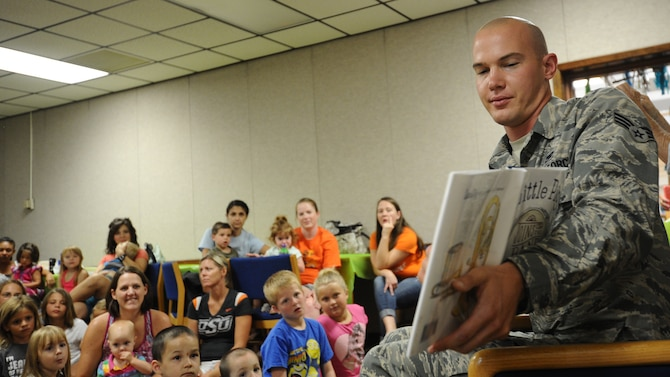 Senior Airman Kristofor Pohl, 325th Maintenance Squadron munitions inspector journeyman, volunteers time to read to children July 8 at the Tyndall Base Library during the Read to the Rhythm program. Read to the Rhythm is a program targeted to develop verbal and reading skills of children sponsored by the 325th Force Support Squadron. (U.S. Air Force photo by Senior Airman Ty-Rico Lea/Released)