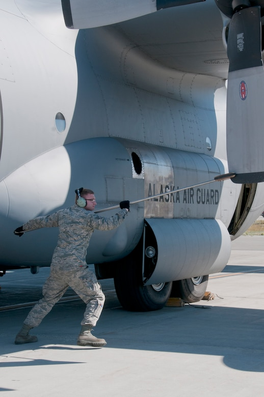 Staff Sgt. Dayton Osborn, a 176th Aircraft Maintenance crew chief, rotates the blades of a C-130 Hercules aircraft on Joint Base Elmendorf-Richardson, Alaska,  Aug. 11, 2015, for operational integrity. Alaska Air Guardsmen of the 176th Wing train alongside their international counterparts as part of Red Flag-Alaska 15-3. (Alaska Air National Guard photo by Tech. Sgt N. Alicia Halla/released)