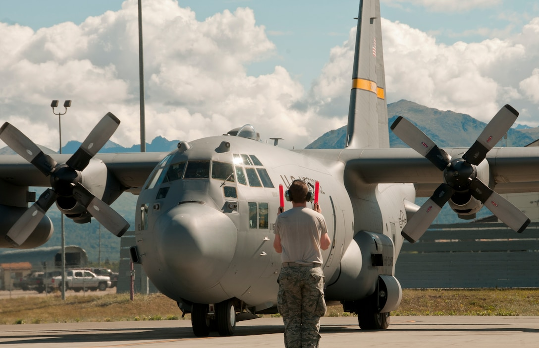A member of the 176th Maintenance Group marshals in a C-130 Hercules aircraft on Joint Base Elmendorf-Richardson, Alaska, Aug. 11, 2015, returning from its morning mission. Alaska Air Guardsmen of the 176th Wing train alongside their international counterparts as part of Red Flag-Alaska 15-3. (Alaska Air National Guard photo by Tech. Sgt N. Alicia Halla/released)