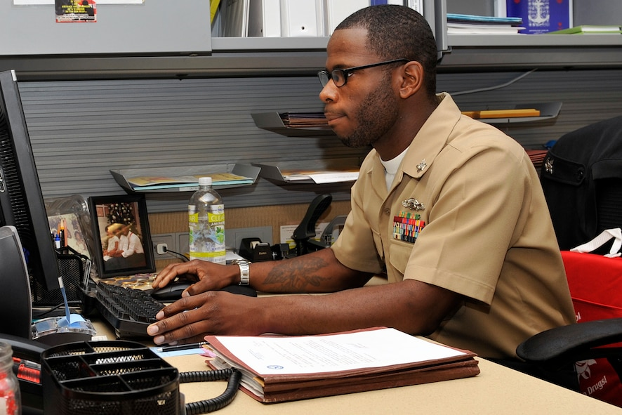 U.S. Navy Petty Officer Second Class Tyrone Ferguson, Naval Operations Support Center – Omaha administrative clerk, downloads some information at his desk July 28. Ferguson is a member of the Omaha Stockmen semi-pro football team. (U.S. Air Force photo by Jeff W. Gates/Released)
