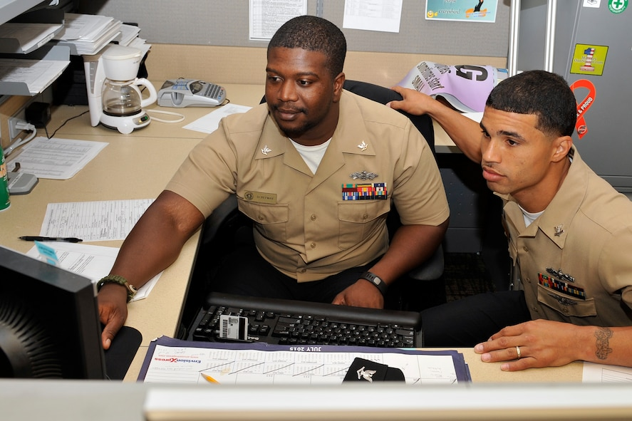 U.S. Navy Petty Officer Deshawn Petway and Petty Officer Ronnie Frost, gather to look at some training records July 28. Petway and Frost are members of the Omaha Stockmen semi-pro football team and work at the Navy Operational Support Center – Omaha, Offutt Air Force Base, Nebraska. (U.S. Air Force photo by Jeff W. Gates/Released)