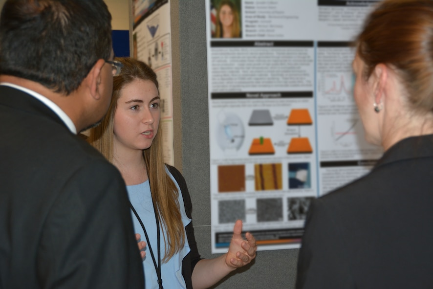 AFRL student researcher Ms. Jennifer Colborn describes her research to members of the Dayton Development Coalition during the August 5 summer student poster session and tour at the AFRL Materials and Manufacturing Directorate.  (AFRL photo by Anise Simpson)