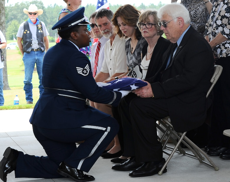 Staff Sgt. Sherring Goodwin, Columbus Air Force Base Honor guardsman, presents the folded American flag to Joe Partridge, brother of the late Capt. Frederick Partridge, Aug. 10 at the Mississippi Veterans Memorial Cemetery. Full honors were presented by the Honor Guardsmen for Partridge to include a flag folding, firing party, color team and a bugle player who finished the ceremony with the playing of Taps. (U.S. Air Force photo/Senior Airman Kaleb Snay)