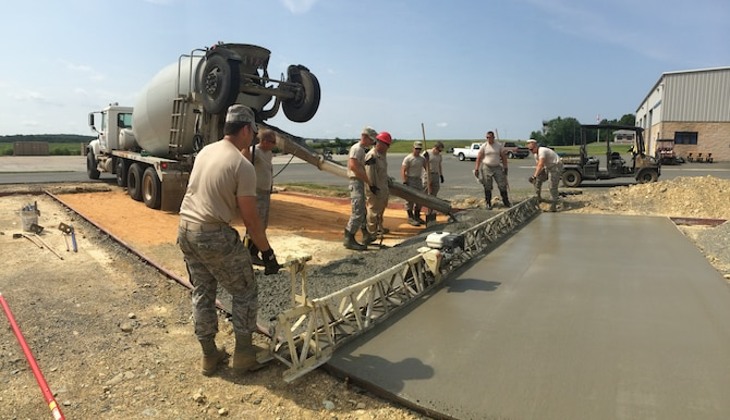 Members of the 138th Civil Engineer Squadron, Tulsa, Okla; place concrete for a new training area at the 145th Regional Training Site, New London, N.C., June 25, 2015. The concrete pad will support the new Rapid Runway Repair Super Kit. 145th and 138th civil engineers participated in a Deployment for Training program that provides contingency type training and gives airmen invaluable hands-on experience that cannot be matched in a traditional drill weekend at home station. (Air National Guard photo courtesy of 138th Civil Engineer Squadron/Released)