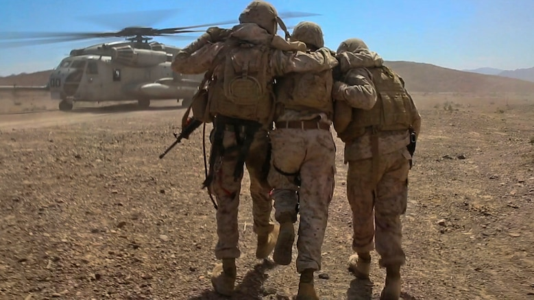 Marines with Combat Logistics Battalion 1, Combat Logistics Regiment 1, 1st Marine Logistics Group, help a simulated casualty to a CH-53E Super Stallion during a casualty evacuation drill at Marine Corps Air Ground Combat Center Twentynine Palms, California, Aug. 10, 2015. A simulated improvised explosive device attack left the Marines with a disabled vehicle and two wounded Marines awaiting evacuation by helicopter.