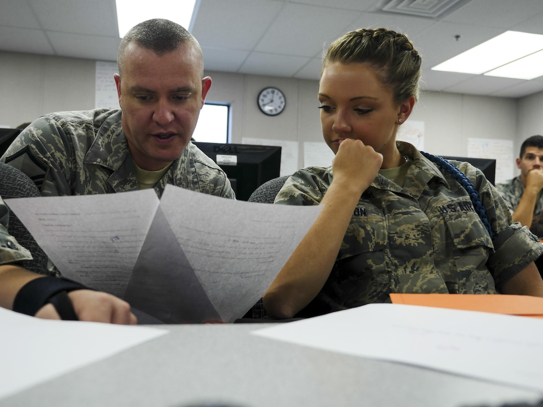 Air Force Master Sgt. Michael Andriacco, Basic Photojournalist Course-Air Force instructor, answers a question from Airman Basic Lauren M. Johnson, BPJC-USAF Class 050-15 student, about a writing assignment at the Defense Information School, Fort George G. Meade, Md., Aug. 6, 2015. BPJC-USAF provides instruction in command information, community engagement, media relations, new writing and basic still photography. (DoD photo by Joseph Coslett/Released)