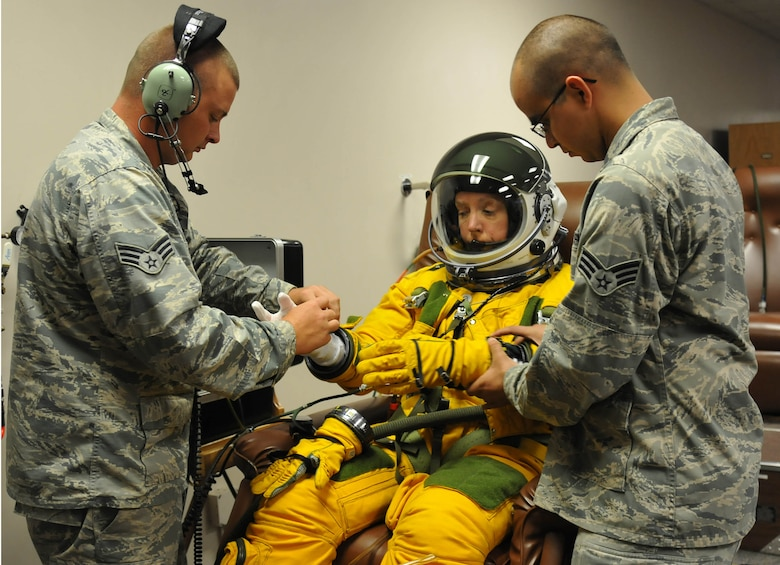 Senior Airmen Aaron Saenz and Kyle Lang, 9th Physiological Support Squadron launch and recovery technicians, help Secretary of the Air Force Deborah Lee James properly dress in a high-altitude pressure suit at Beale Air Force Base, Calif., Aug. 11, 2015. The specialized pressure suit allows U-2S pilots to safely fly at altitudes reaching 70,000 feet. James visited Beale AFB to receive a first-hand perspective of high-altitude intelligence, surveillance and reconnaissance from collection to dissemination. (U.S. Air Force photo/Senior Airman Dana J. Cable)
