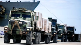 U.S. Marine 7-ton trucks with Combat Logistics Battalion 31, 31st Marine Expeditionary Unit, prepare to distribute water and supplies from the USS Ashland to local civilians as part of typhoon relief efforts in Saipan, Aug. 11, 2015. The 31st MEU and the ships of the Bonhomme Richard Amphibious Ready Group are assisting the Federal Emergency Management Agency with distributing emergency relief supplies to Saipan after the island was struck by Typhoon Soudelor Aug. 2-3.