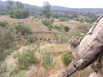 Marines move from their security position in a single file line in preparation to assault their last objective point.