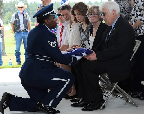 Staff Sgt. Sherring Goodwin, a honor guardsman from Columbus Air Force Base, Mississippi, presents the folded American flag to Joe Partridge, the brother of the late Capt. Frederick Partridge, Aug. 10, 2015, at the Mississippi Veterans Memorial Cemetery. Full honors were presented for Frederick, to include a flag folding, firing party, color team and a bugle player who finished the ceremony with the playing of Taps. (U.S. Air Force photo/Senior Airman Kaleb Snay)