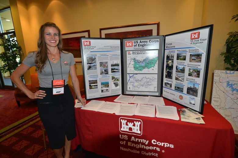 Lacey Thomason, planning project manager, Plans, Formulations Section Nashville District stands near the Corps of Engineers booth during the 6th Annual TN Association of Floodplain Managers Conference in Murfreesboro, Tenn. Aug. 11-14, 2015.