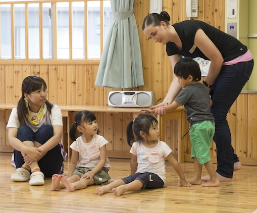 Pfc. Makayla Whitney, a postal clerk with Headquarters and Headquarters Squadron based aboard Marine Corps Air Station Iwakuni, Japan, shows students at Josho Hoikuen School in Iwakuni City, how to play duck, duck, goose during a community relations event hosted by the Marine Memorial Chapel, Aug. 11, 2015. Service members commit to building positive relationships with the local community by participating in these events.