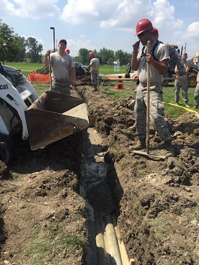 Members of the 200th RED HORSE, Camp Perry, OH, gather for a Unit Training Assembly, July 11, 2015. Heavy Equipment is used to dig out the location for a manhole to be placed. (Photos courtesy 2nd Lt. Ashley Klase)