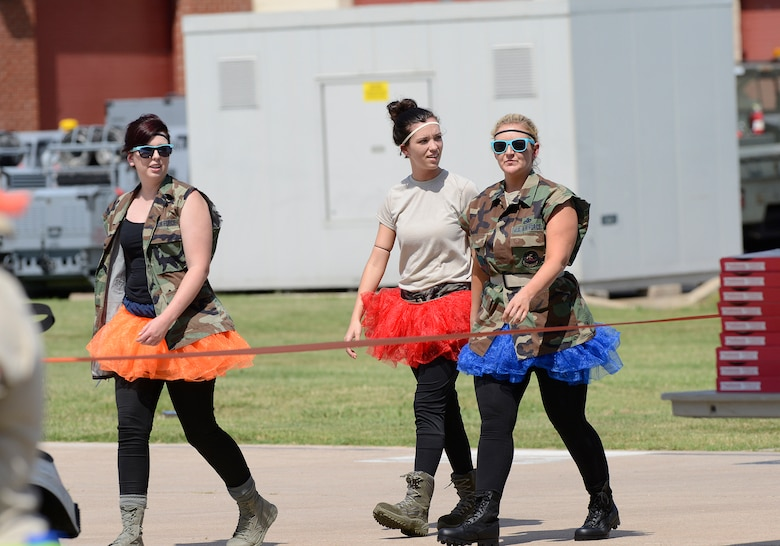 Senior Airman Erin Crews (left), Airman 1st Class Natasha Applegate (center) and Master Sgt. Christine Cook (right) survey the festivities as they prepare to enter the 138th Fighter Wing's combat dining-in held Aug. 1, 2015 at the Tulsa Air National Guard base.  The wing's senior non-commissioned officer's council sponsored the event as a way to enhance camaraderie and promote esprit de corps throughout the ranks.   (U.S. National Guard photo by Master Sgt. Mark A. Moore/Released)